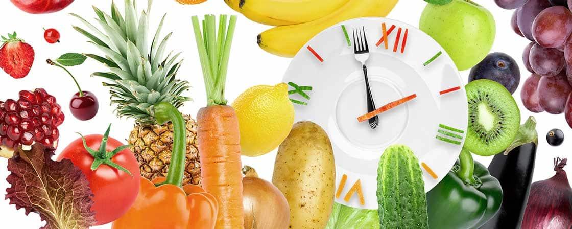 głodówka lecznicza, post przerywany zilustrowany jako zegar wykonany z talerz i sztućców otoczonych kolorowymi warzywami i owocami