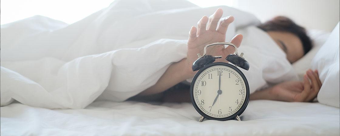 depresja a rym dobowy spiący człowiek z ręką na budziku